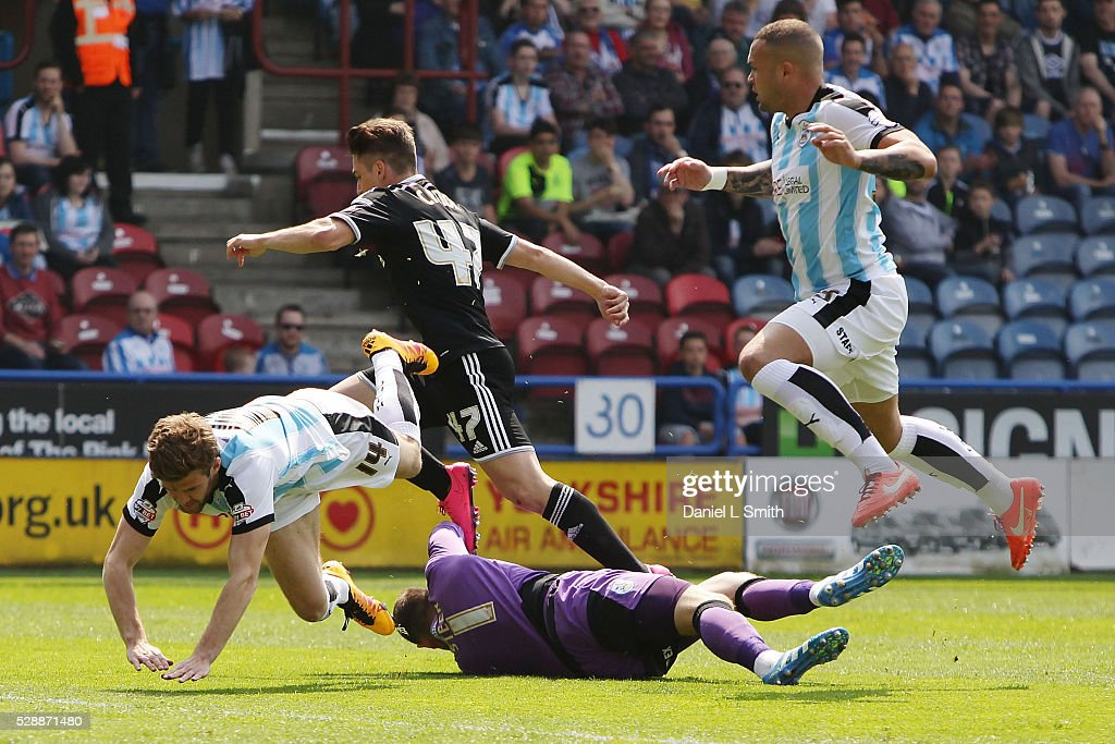 Jed Steer of Huddersfield Town FC saves a goal as Martin Cranie and Joel Lynch of Huddersfield Town FC leap over him during the Sky Bet Championship match between Huddersfield Town and Brentford at The John Smith's Stadium on May 7, 2016 in Huddersfield, United Kingdom.