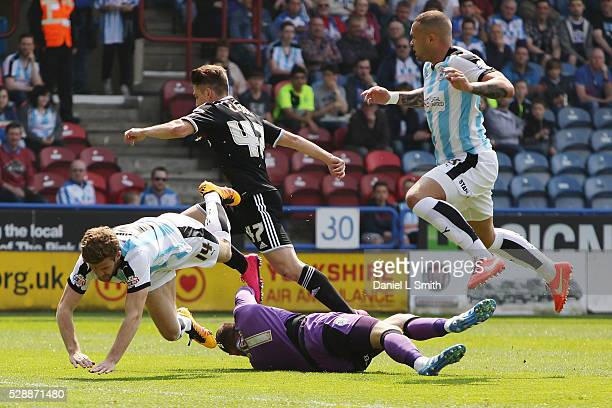 Jed Steer of Huddersfield Town FC saves a goal as Martin Cranie and Joel Lynch of Huddersfield Town FC leap over him during the Sky Bet Championship...