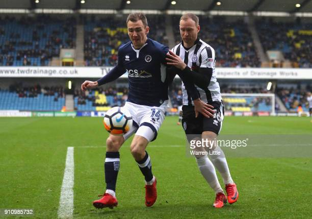 Jed Wallace of Millwall is challenged by Matt Done of Rochdale AFC during The Emirates FA Cup Fourth Round match between Millwall and Rochdale AFC at...