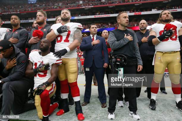 Jed York of the San Francisco 49ers stands with his team in solidarity on the sideline during the anthem prior to the game against the Arizona...