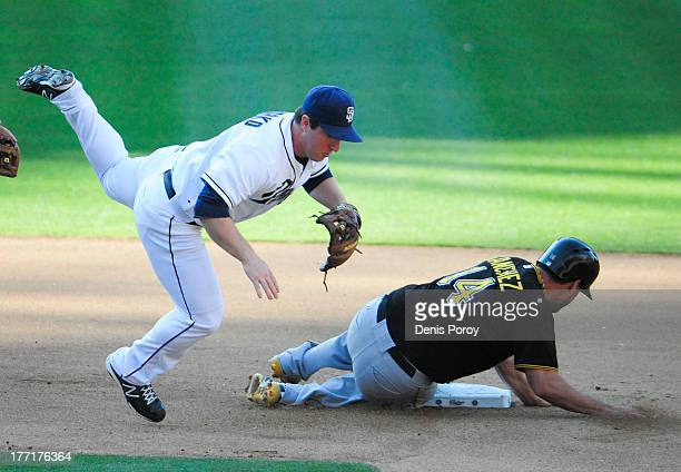 Jedd Gyorko of the San Diego Padres jumps over Gaby Sanchez of the Pittsburgh Pirates as he tries to turn a double play during the seventh inning of...