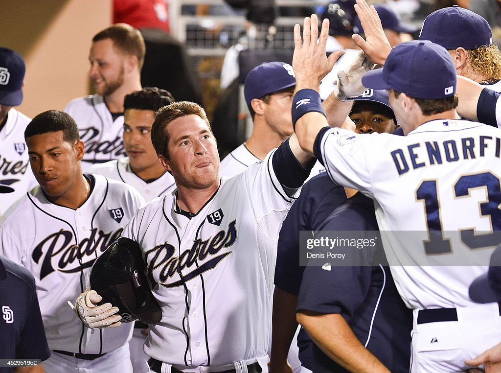 Jedd Gyorko #9 of the San Diego Padres, left, is congratulated in the dugout after hitting a solo home run during the fourth inning of a baseball game against the St. Louis Cardinals at Petco Park July 30, 2014 in San Diego, California.