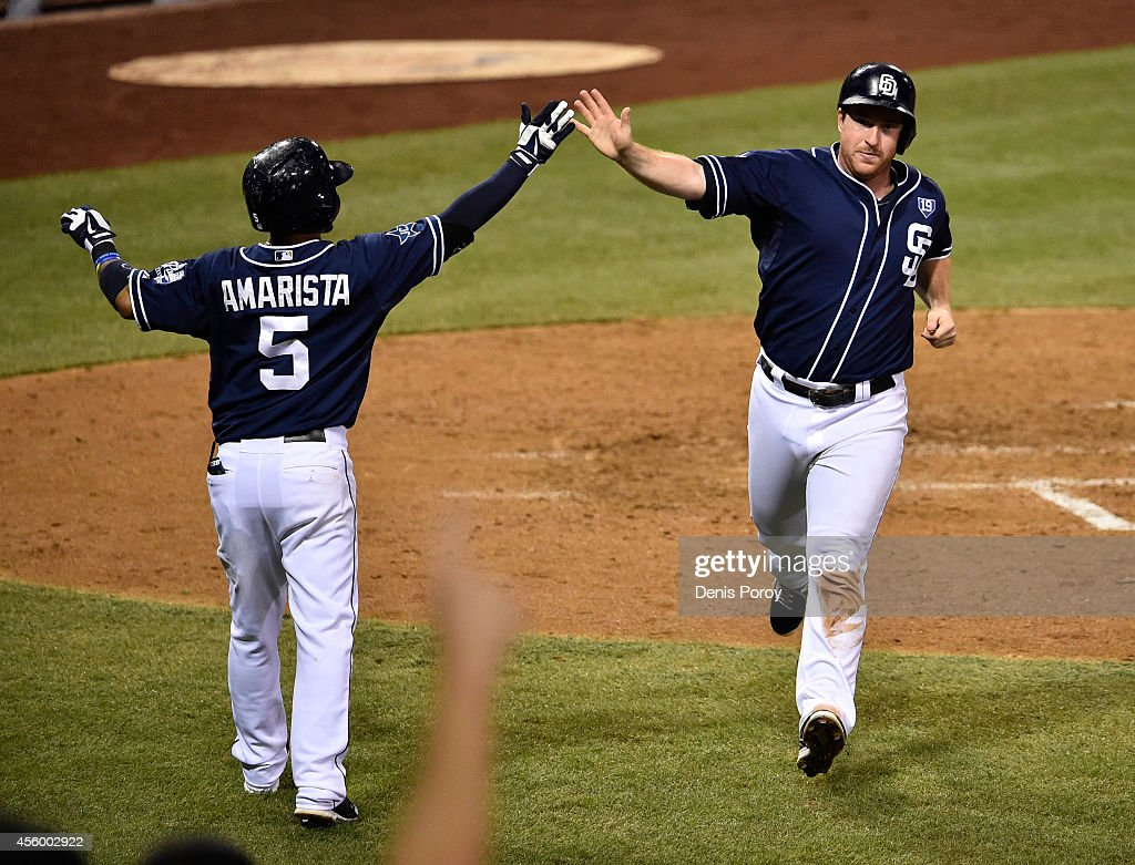 Jedd Gyorko #9 of the San Diego Padres, right, is congratulated by Alexi Amarista #5 after scoring during the sixth inning of a baseball game against the Colorado Rockies at Petco Park September, 23, 2014 in San Diego, California.