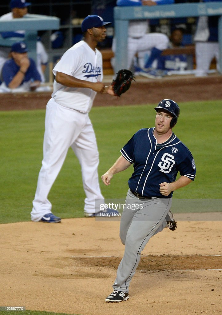 Jedd Gyorko #9 of the San Diego Padres scores a run to take a 1-0 lead in front of pitcher Roberto Hernandez #55 of the Los Angeles Dodgers during the second inning at Dodger Stadium on August 20, 2014 in Los Angeles, California.