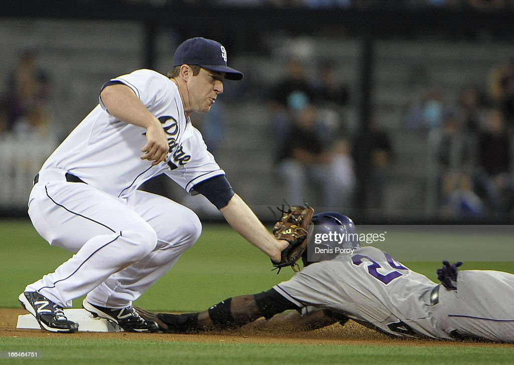 Jedd Gyorko #9 of the San Diego Padres tags out Dexter Fowler #24 of the Colorado Rockies as he tries to steal second base in the first inning of a baseball game at Petco Park on April 12, 2013 in San Diego, California.