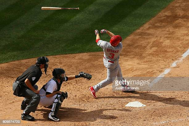 Jedd Gyorko of the St Louis Cardinals loses control of his bat as catcher Tom Murphy of the Colorado Rockies and home plate umpire Chad Fairchild...