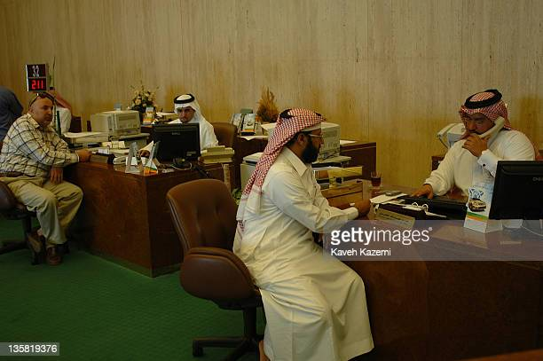 Clients sit at the NCB bank clients' desk in Jeddah, Saudi Arabia, 2nd December 2005.