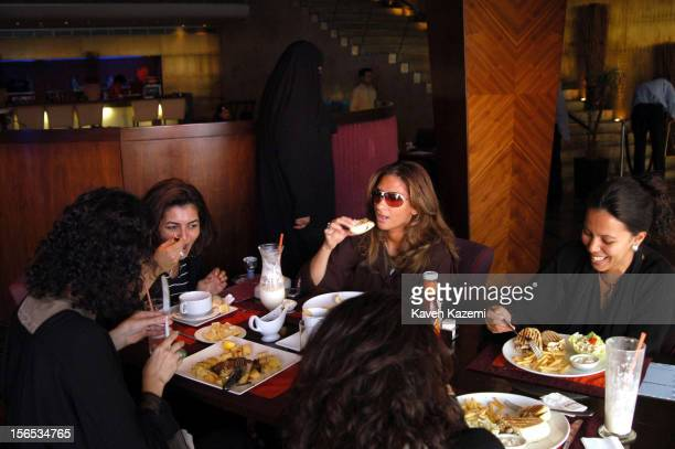 Saudi women with their traditional black abayas and veils off sit at a table having lunch in a modern Corniche district restaurant in Jeddah Saudi...