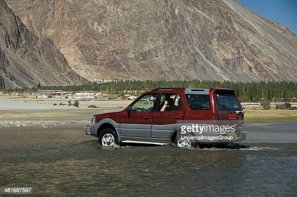 Jeep passing through a lake with mountain range in the background Hunder Nubra Valley Ladakh Jammu and Kashmir India