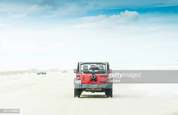 jeep wrangler driving across carova beach - jeep wrangler stock photos and pictures
