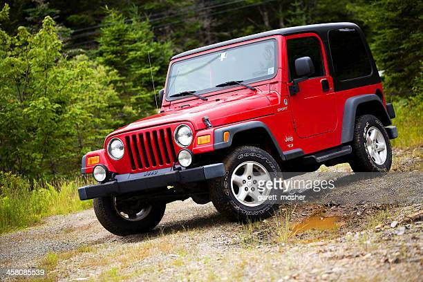 jeep wrangler tj sitting on muddy dirt and gravel trail - jeep wrangler stock photos and pictures