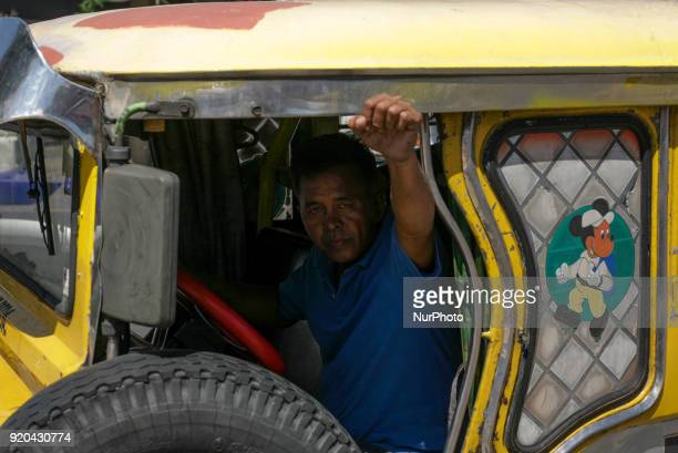 A jeepney driver raises his fist to express his support for jeepney drivers belonging to the activist jeepney driver group PISTON holding a protest...