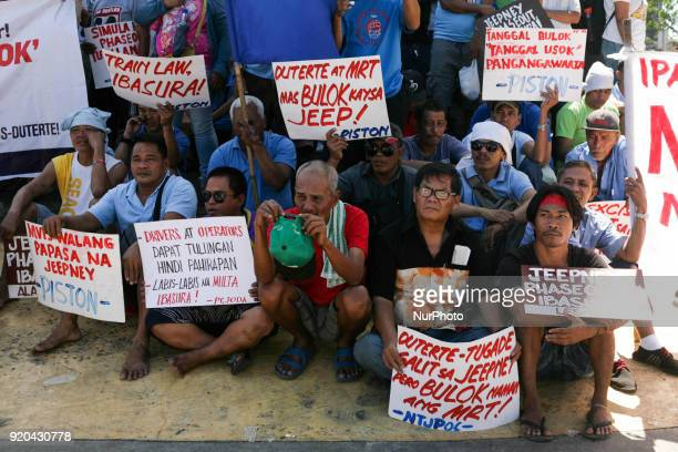 Jeepney drivers belonging to the activist jeepney driver group PISTON hold placards as they listen to a speech during a protest against the...