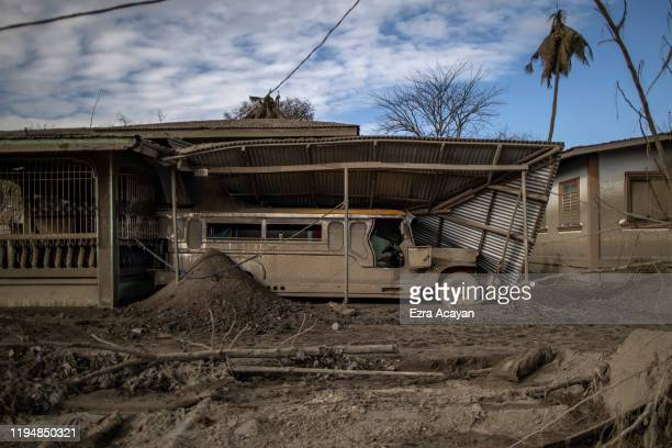 A jeepney is seen parked inside a garage whose roof has collapsed due to heavy volcanic ash from Taal Volcano's eruption on January 20 2020 in the...