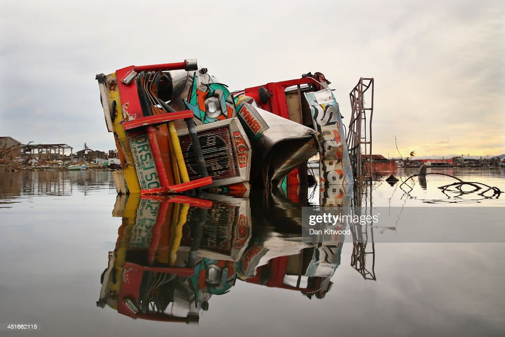 A Jeepney smashed by Typhoon Haiyan lies in the water in Tacloban on November 23, 2013 in Leyte, Philippines. The Jeepney is a modified form of transport based on the military jeep used by US troops during WWII. It has become the primary mode of transport across the Philippines and part of their national identity. Typhoon Haiyan which ripped through Philippines over a week ago has been described as one of the most powerful typhoons ever to hit land, leaving thousands dead and hundreds of thousands homeless. Countries all over the world have pledged relief aid to help support those affected by the typhoon however damage to the airport and roads have made moving the aid into the most affected areas very difficult. With dead bodies left out in the open air and very limited food, water and shelter, health concerns are growing.