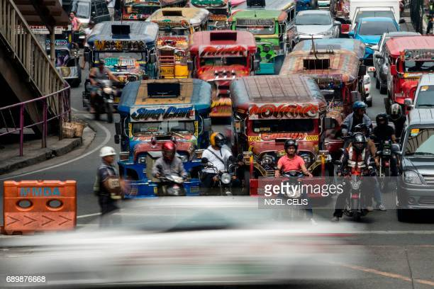 Jeepneys are seen as an enforcer manages traffic at a busy street in Manila on May 30 2017 Jeepneys once hailed as the 'King of the Road' and a...