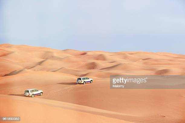Jeeps driving through the sand dunes in the desert near Dubai. United Arab Emirates