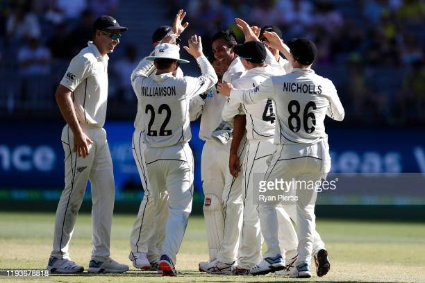 Jeet Raval of New Zealand takes the wicket of Pat Cummins of Australia during day two of the First Test match between Australia and New Zealand at...