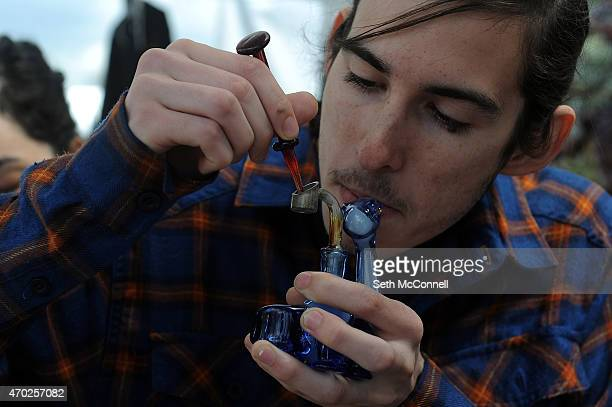 Jef Debrabander does a dab at a booth during the High Times Cannabis Cup at the Denver Mart in Denver Colorado on April 18 2015 The High Times...