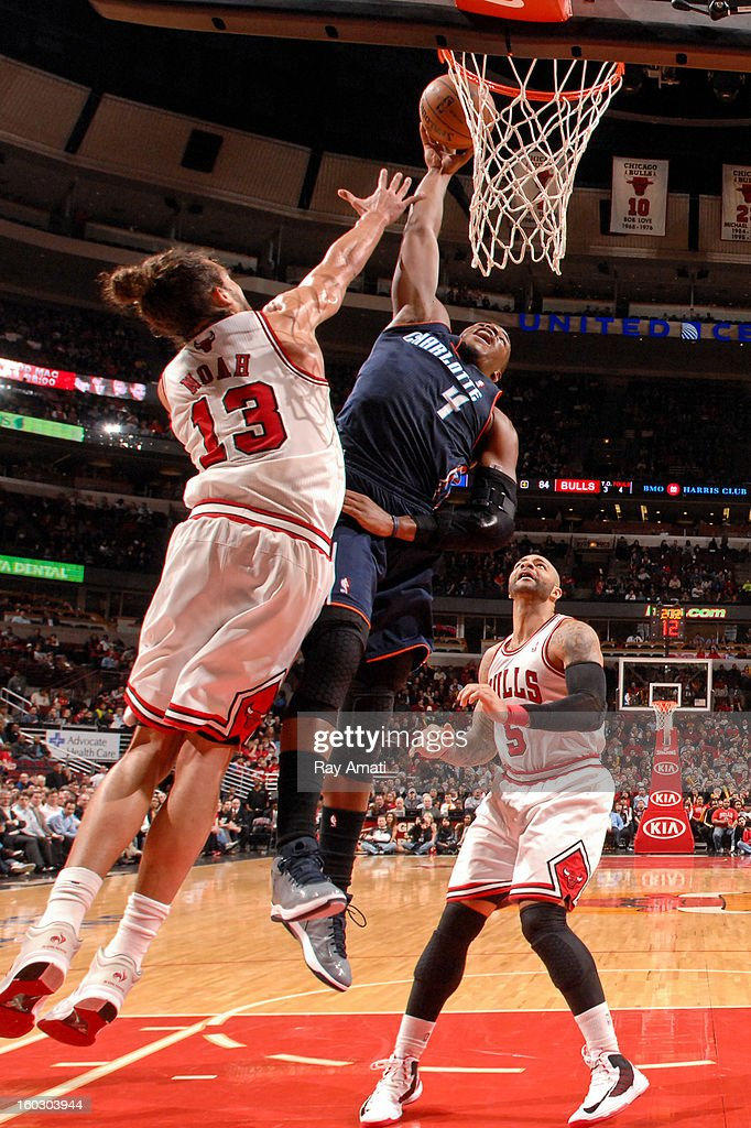 Jeff Adrien #4 of the Charlotte Bobcats rises for a dunk against Joakim Noah #13 and Carlos Boozer #5 of the Chicago Bulls on January 28, 2013 at the United Center in Chicago, Illinois.