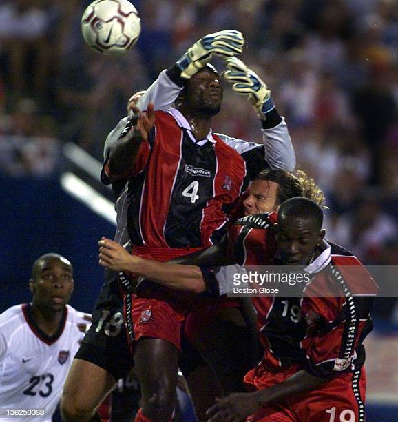 Jeff Agoos of the United States head visible in the middle gets crunched by Trinidad and Tobago's Marvin Andrews #4 and Dwight Yorke #19 while...