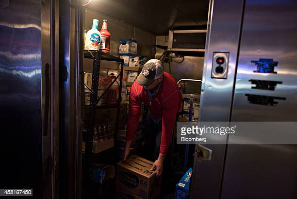 Jeff Allen a delivery driver for Brewers Distributing Co stacks cases of AnheuserBusch beer in the cooler at Pottsies Place in Pekin Illinois US on...