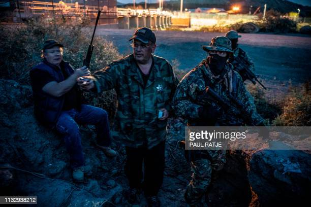 Jeff Allen Jim Benvie Viper and Stinger share cigarettes while patrolling the USMexico border in Sunland Park New Mexico on March 20 2019 The militia...