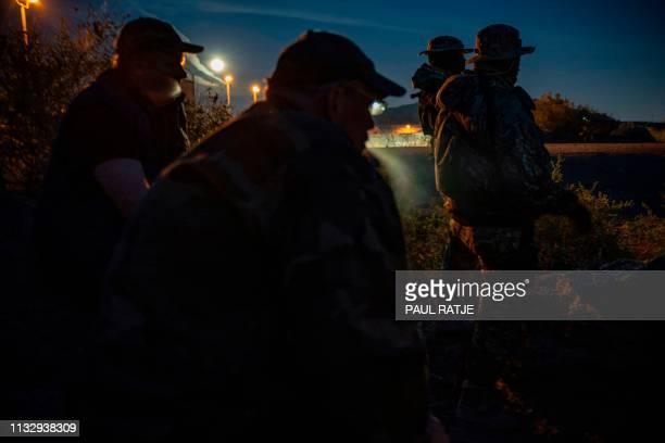 Jeff Allen Jim Benvie Viper and Stinger share cigarettes while patrolling the USMexico border in Sunland Park New Mexico on March 20 2019 The militia...