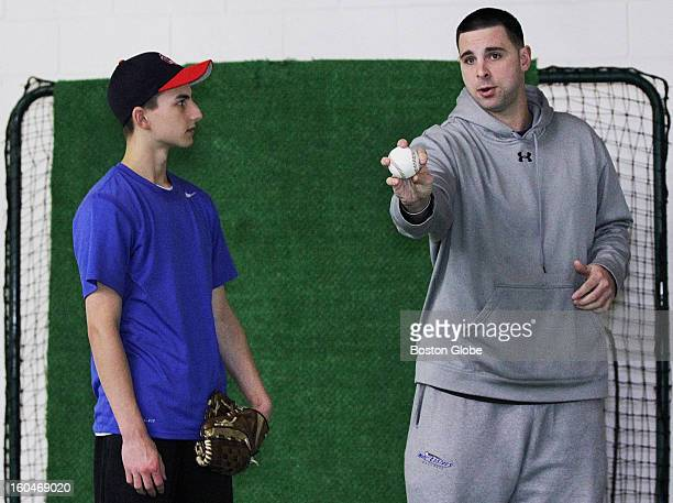 Jeff Allison right pointed out a few moves on a curve ball during a lesson with Eric Ell at the Extra Innings baseball facility in Tewksbury Saturday...