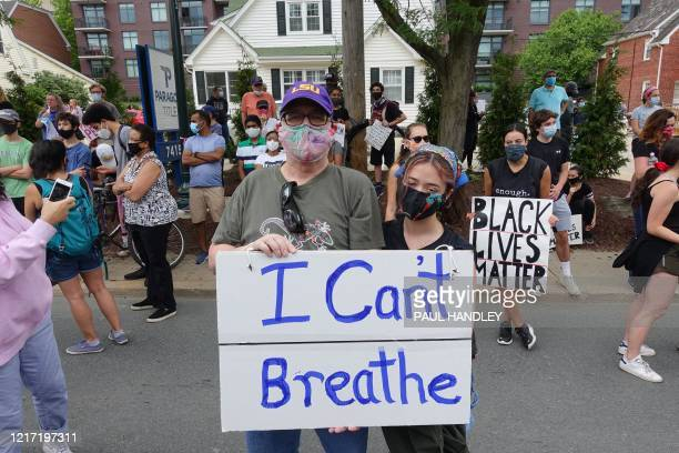 "Jeff Austin and his daughter Lily Henry-Austin of Silver Spring, hold a sign reading ""I Can't Breathe"" as they protest police brutality against..."