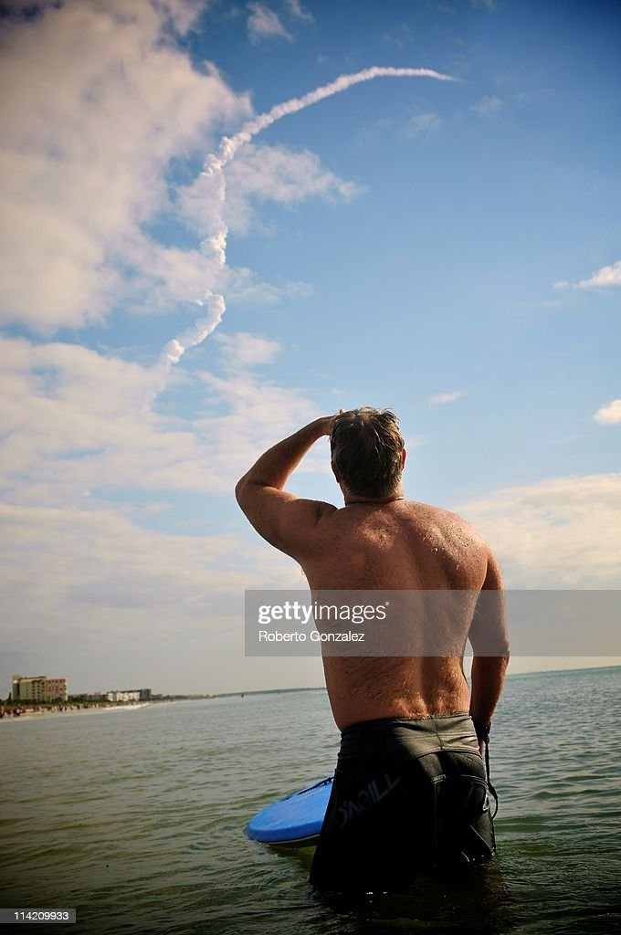 Jeff Barber of Virginia Beach watches from the water as NASA Space Shuttle Endeavour launches from Kennedy Space Center May 16, 2011 in Cocoa Beach, Florida. Endeavour embarked on its final flight to the International Space Station on May 16. Mission STS-134 will deliver the Express Logistics Carrier-3 (ELC-3) and the Alpha Magnetic Spectrometer (AMS-2) to the International Space Station. Arizona congresswoman Gabrielle Giffords, who is married to Endeavour Commander Mark Kelly, is recovering from an attempted homicide and will be attending the launch.