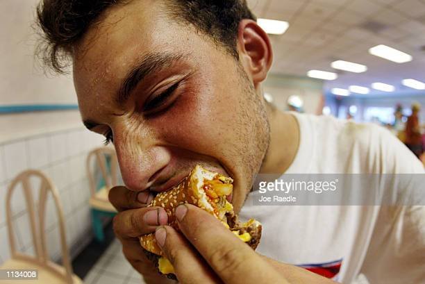 Jeff Baughman bites into his double cheeseburger with a Super Fries and a Super Coke on July 18 2002 at a McDonalds in Miami Beach Florida The health...