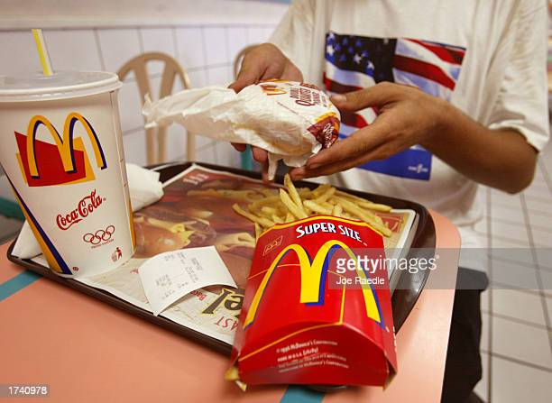 Jeff Baughman unwraps his double quarterpounder with cheese, a super fries and a super coke at a McDonald's restaurant July 18, 2002 in Miami Beach,...