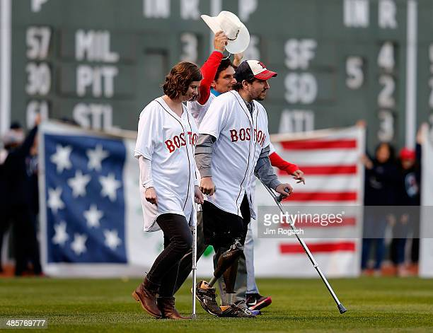 Jeff Bauman and other survivors along with first responder Carlos Arredondo react during the 2013 Boston Marathon bombing ceremony at Fenway Park...