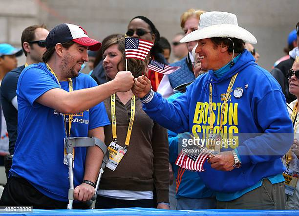 Jeff Bauman, left, a survivor of last year's bombings, holds an American flag while he fist bumps Carlos Arredondo, who saved his life, as they meet...
