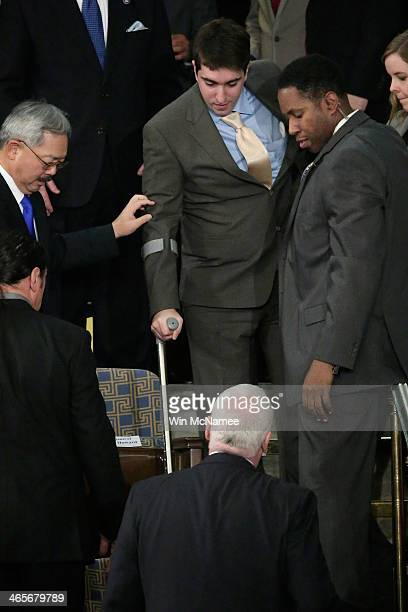 Jeff Bauman who was injured during the Boston bombing is helped to his seat before US President Barack Obama to deliver the State of the Union...