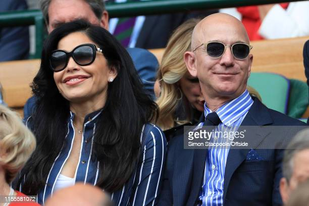 Jeff Bezos and his partner Lauren Sanchez look on from the Royal Box on Centre Court on Day 13 of The Championships Wimbledon 2019 at the All England...