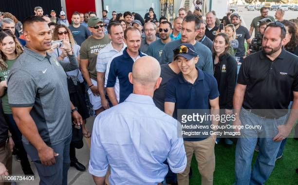 Jeff Bezos founder and CEO of Amazon bottom shakes hands with Amazon employees after he made a surprise appearance during a Amazon Veterans Day...