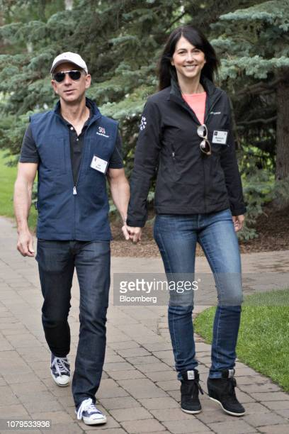 Jeff Bezos founder and chief executive officer of Amazoncom Inc left holds hands with his wife MacKenzie Bezos while arriving for a morning session...