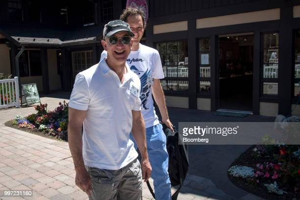 Jeff Bezos founder and chief executive officer of Amazoncom Inc left and John Elkann chairman of Fiat Chrysler Automobiles NV walk the grounds after...