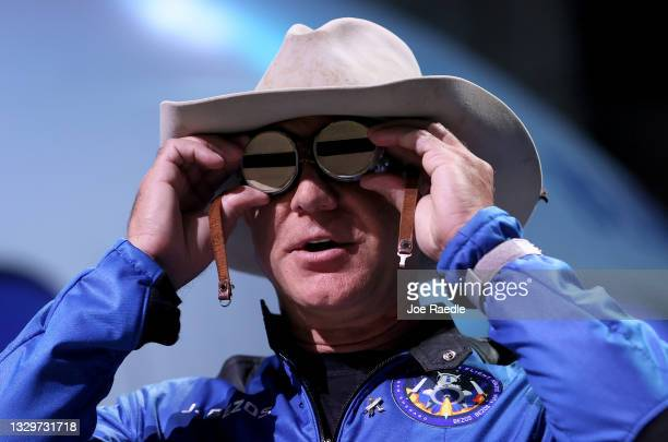 Jeff Bezos holds the aviation glasses that belonged to Amelia Earhart as he speaks during a press conference about his flight on Blue Origin's New...