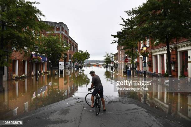 Jeff Bigler turns his bicycle around after taking in the scene of a tidal flooded King Street on Tuesday September 11, 2018 in Alexandria, VA.