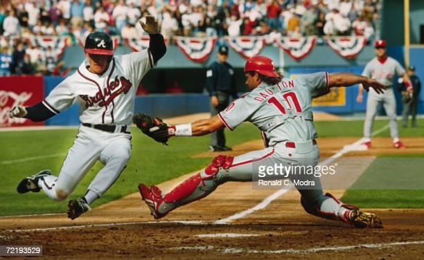 Jeff Blauser of the Atlanta Braves slides into home plate as Darren Daulton of the Philadelphia Phillies tries to tag him at Fulton County Stadium...