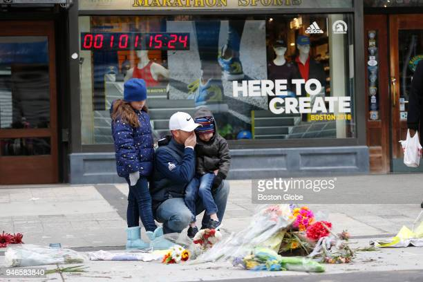 Jeff Breese kneels at a memorial for the victims of the Boston Marathon bombing with his two children Everett and Mallory on April 15 the five year...
