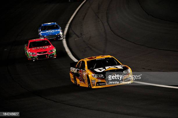 Jeff Burton driver of the Caterpillar Chevrolet leads Danica Patrick driver of the GoDaddy Breast Cancer Awareness Chevrolet and Aric Almirola driver...