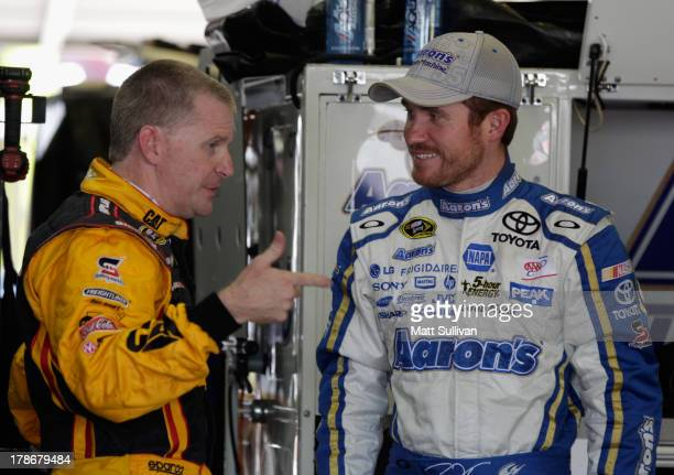 Jeff Burton driver of the Caterpillar Chevrolet speaks with Brian Vickers driver of the Aaron's Dream Machine Toyota in the garage area during...
