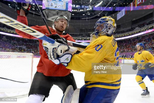 Jeff Carter of Canada collides with Henrik Lundqvist of Sweden during the Men's Ice Hockey Gold Medal match on Day 16 of the 2014 Sochi Winter...