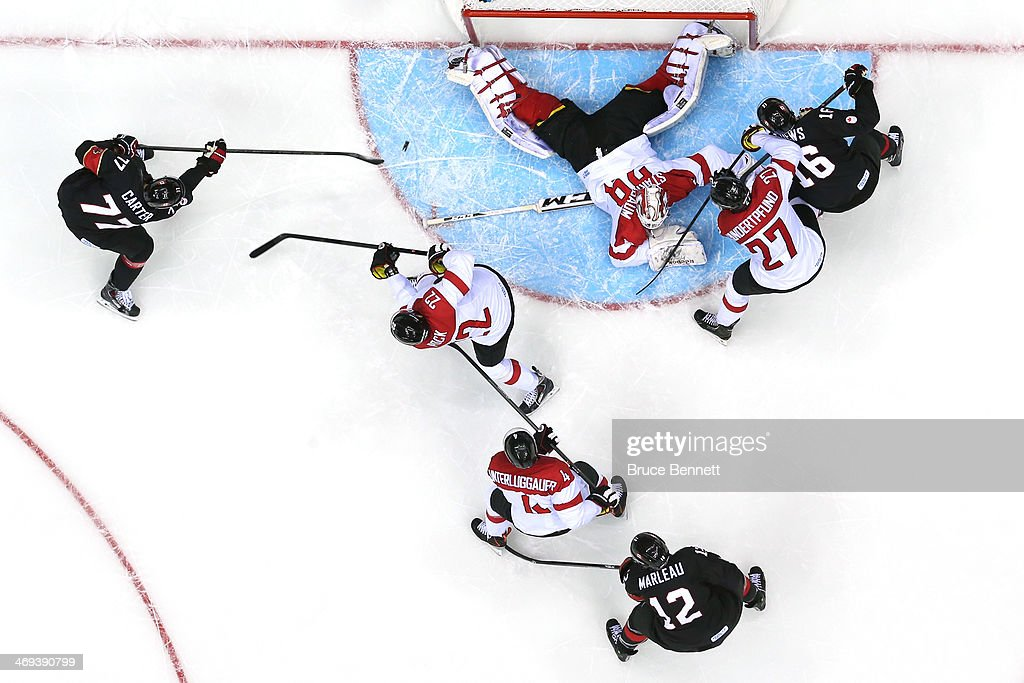 Jeff Carter #77 of Canada scores a goal in the second period against Bernhard Starkbaum #29 of Austria during the Men's Ice Hockey Preliminary Round Group B game on day seven of the Sochi 2014 Winter Olympics at Bolshoy Ice Dome on February 14, 2014 in Sochi, Russia.