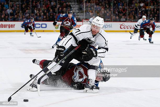 Jeff Carter of the Los Angeles Kings controls the puck as Matt Duchene of the Colorado Avalanche is penalized for tripping in the first period at...