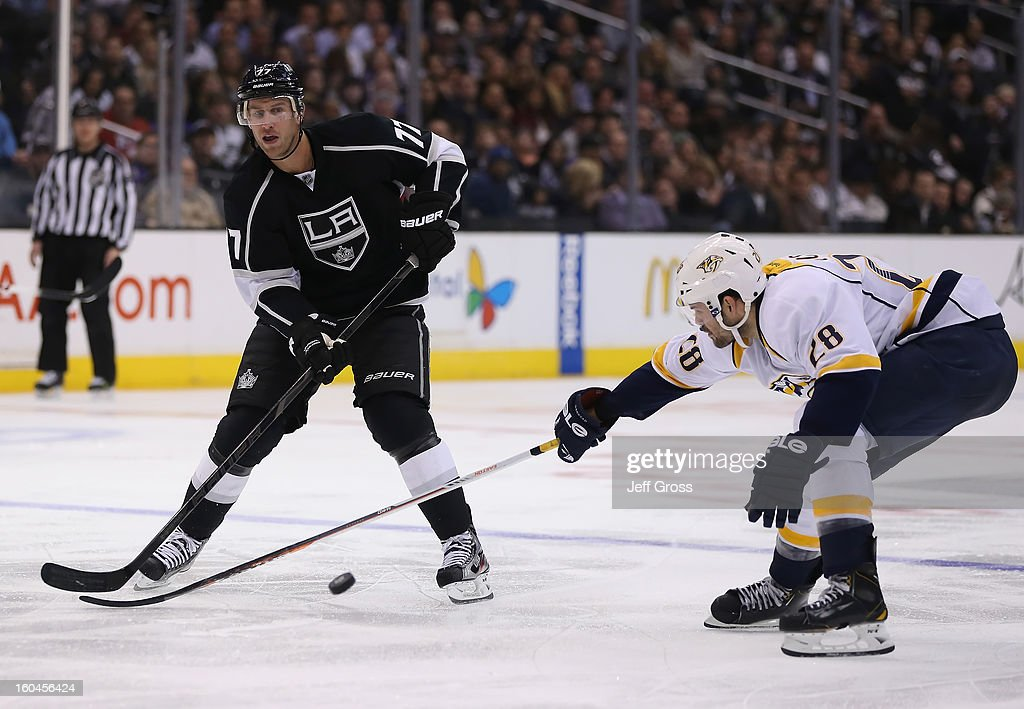 Jeff Carter #77 of the Los Angeles Kings passes the puck past Paul Gaustad #28 of the Nashville Predators in the second period at Staples Center on January 31, 2013 in Los Angeles, California. The Predators defeated the Kings 2-1 in a shootout.